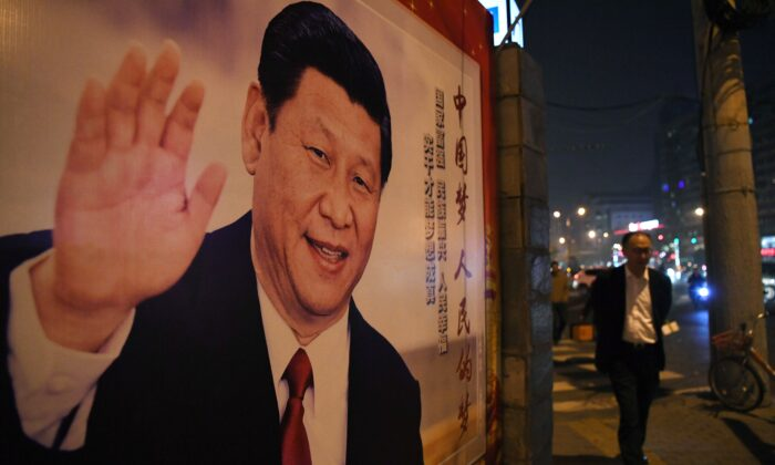 A man walks past a roadside poster of Chinese leader Xi Jinping after the closing of the 19th Communist Party Congress in Beijing on Oct. 24, 2017. (GREG BAKER/AFP via Getty Images)