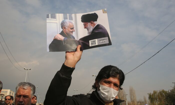 A man holds a picture of Iran's supreme leader Ayatollah Ali Khamenei with Iranian Revolutionary Guards Major General Qassem Soleimani (L) during a demonstration in Tehran on Jan. 3, 2020.  Atta Kenare/AFP via Getty Images