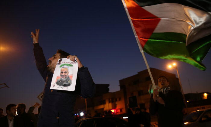 A man holds a picture of late Iranian General Qassem Soleimani, as people celebrate in the street after Iran launched missiles at U.S.-led forces in Iraq, in Tehran, Iran on Jan. 8, 2020. (Nazanin Tabatabaee/WANA (West Asia News Agency) via Reuters)
