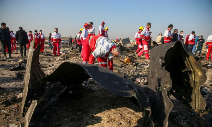 Red Crescent workers check the debris from the Ukraine International Airlines plane, that crashed after take-off from Iran's Imam Khomeini airport, on the outskirts of Tehran, Iran on Jan. 8, 2020. (Nazanin Tabatabaee/WANA (West Asia News Agency) via Reuters)