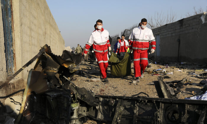 Rescue workers carry the body of a victim of an Ukrainian plane crash among debris of the plane in Shahedshahr, southwest of the capital Tehran, Iran on Jan. 8, 2020. (Ebrahim Noroozi/AP Photo)