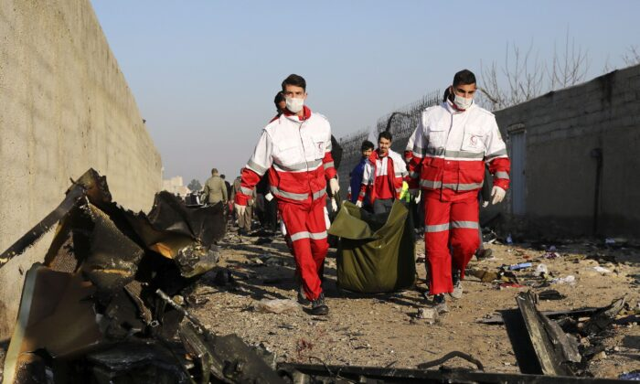 Rescue workers carry the body of a victim of a Ukrainian plane crash among debris of the plane in Shahedshahr, southwest of Tehran, Iran, on Jan. 8, 2020. The plane carrying 176 people crashed on Jan 7 shortly after takeoff from Tehran's main airport, killing all on board. (AP Photo/Ebrahim Noroozi)