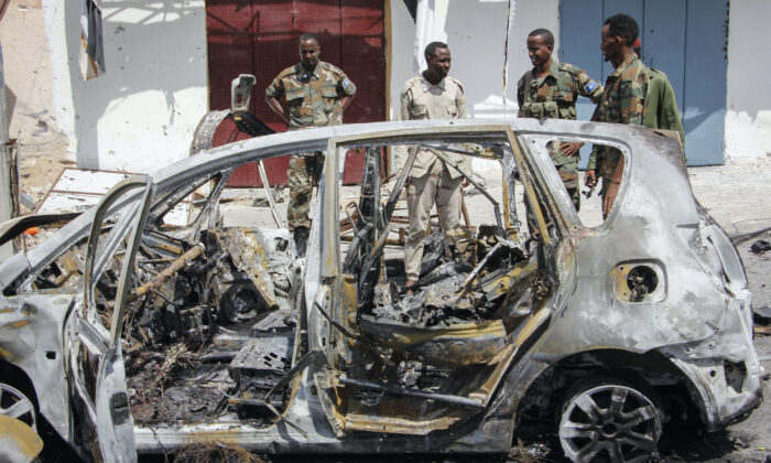 Security forces and others stand by the wreckage of vehicles after a vehicle bomb attack on a security checkpoint located near the presidential palace, in Mogadishu, Somalia on Wednesday, Jan. 8, 2020. (Farah Abdi Warsameh/AP)