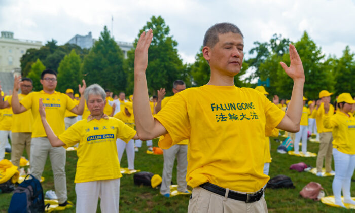 Falun Gong practitioners perform the exercises at a rally commemorating the 20th anniversary of the persecution of Falun Gong in China, on the West Lawn of Capitol Hill on July 18, 2019. (Mark Zou/The Epoch Times)