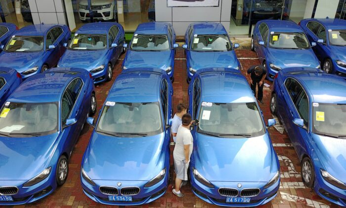"""People look at a BMW 1-Series """"car-sharing"""" in Shenyang in China's northeastern Liaoning Province on Aug. 10, 2017. (STR/AFP via Getty Images)"""