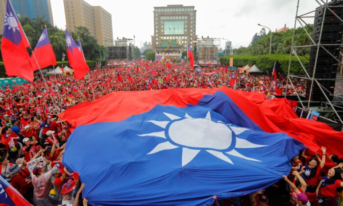 Supporters of Kaohsiung city mayor Han Kuo-yu from the Kuomintang Party display Taiwanese flags during a campaign event in Taipei on June 1, 2019.  Daniel Shih/AFP via Getty Images