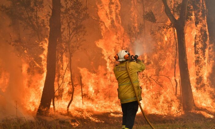 """A firefighter conducts back-burning measures to secure residential areas from encroaching bushfires in the Central Coast, some 90-110 kilometres north of Sydney on Dec. 10, 2019. Toxic haze blanketed Sydney on Dec. 10 triggering a chorus of smoke alarms to ring across the city, as Australians braced for """"severe"""" weather conditions expected to fuel deadly bush blazes. (Saeed Khan/via Getty Images)"""