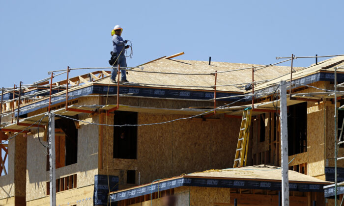 A worker walks on the roof of a new home under construction in Carlsbad, Cali., on Sept. 22, 2014. (Reuters/Mike Blake)