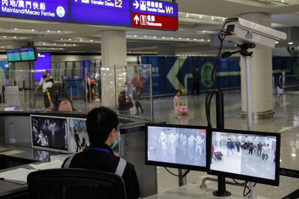 A health surveillance officer monitors passengers arriving at the Hong Kong International airport