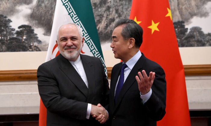 China's Foreign Minister Wang Yi shakes hands with Iran's Foreign Minister Mohammad Javad Zarif during a meeting at the Diaoyutai state guest house in Beijing, China on Dec. 31, 2019. (Noel Celis-Pool/Getty Images)