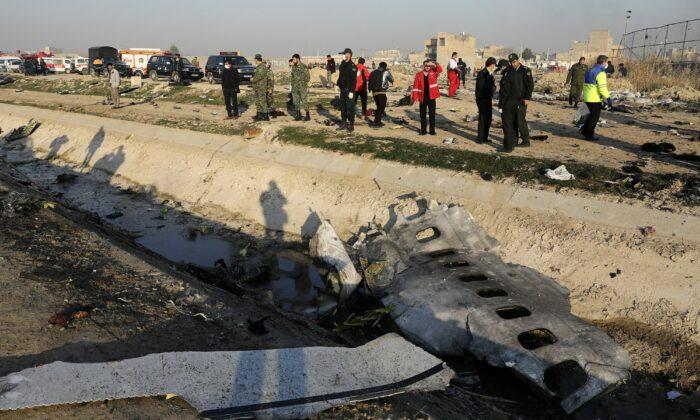 Debris is seen from an Ukrainian plane which crashed as authorities work at the scene in Shahedshahr, southwest of the capital Tehran, Iran on Jan. 8, 2020. (Ebrahim Noroozi/AP Photo)