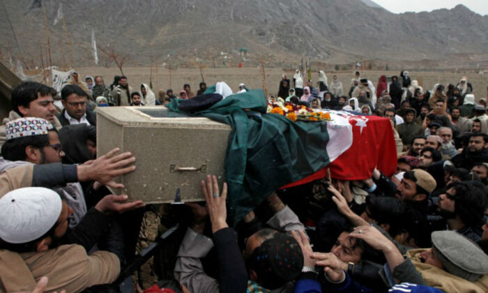 Relatives and neighbors reach out to carry the coffin of a police officer who was killed with others by a bomb blast in a mosque, during a funeral in Quetta, Pakistan on Jan. 11, 2020. (Naseer Ahmed/Reuters)