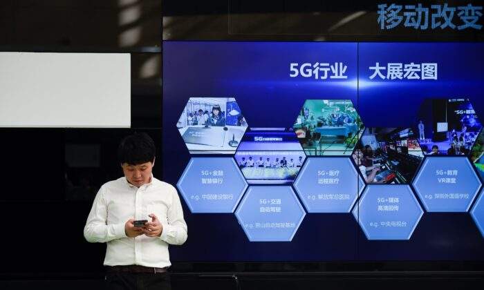 A man uses his mobile phone in front of a screen showing China's 5G industry outside a telecom office in Beijing on Sept. 25, 2019. (WANG ZHAO/AFP via Getty Images)