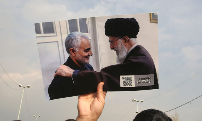 A man holds a picture of Iran's supreme leader Ayatollah Ali Khamenei (R) with Iranian Revolutionary Guards top commander Qassem Soleimani during a demonstration in Tehran on Jan. 3, 2020.  Atta Kenare/AFP via Getty Images