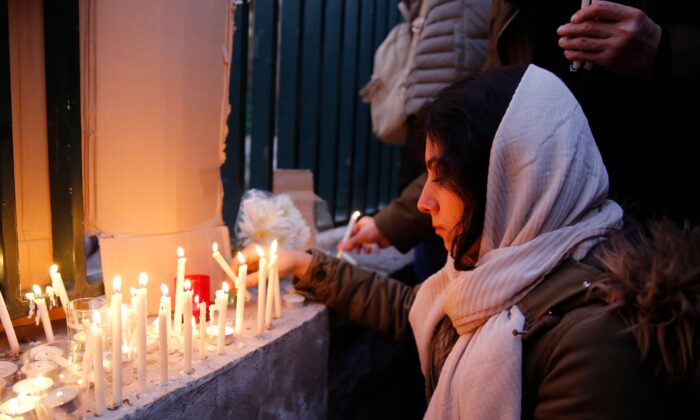 An Iranian lights candles for the victims of Ukraine International Airlines Boeing 737 during a gathering in front of the Amirkabir University in the capital Tehran, on Jan. 11, 2020. (AFP via Getty Images)