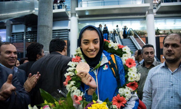 Kimia Alizadeh who became the first Iranian woman ever to win an Olympic medal, shows her medal upon her arrival at Imam Khomeini International Airport Tehran, on Aug. 26, 2016. (Peyman/AFP via Getty Images)