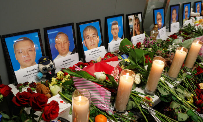 Flowers and candles are placed in front of the portraits of the flight crew members of the Ukraine International Airlines Boeing 737-800 plane that crashed in Iran, at a memorial at the Boryspil International Airport outside Kiev, Ukraine, on Jan. 11, 2020. (Valentyn Ogirenko/Reuters)