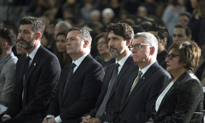 (L-R) Edmonton Mayor Don Iveson, Alberta Premier Jason Kenney, Prime Minister Justin Trudeau, and University of Alberta President David Turpin listen to speeches during a memorial for the victims of the Ukrainian plane disaster in Iran this past week, in Edmonton on Jan. 12, 2020. (The Canadian Press/Todd Korol)