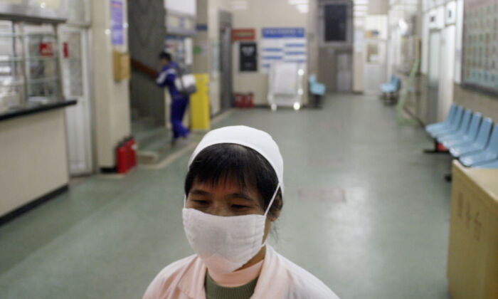 A nurse wearing a face mask, walks in a hallway of a hospital in Guangzhou, China on Jan. 13, 2004. (Getty Images)