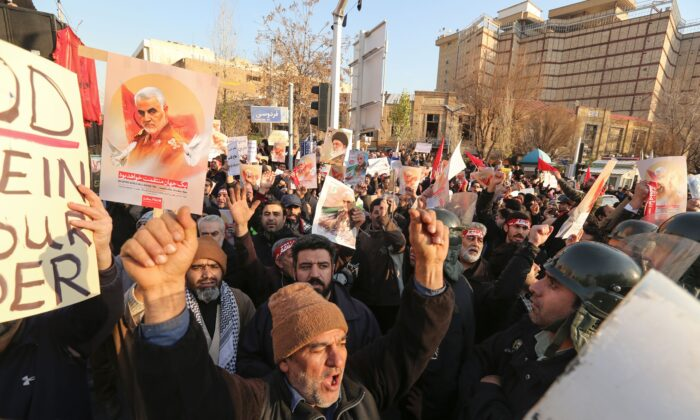 Iranian demonstrators hold placards bearing the image of slain military commander Qasem Soleimani in front of the British embassy in the capital Tehran on Jan. 12, 2020 following the British ambassador's arrest for allegedly attending an illegal demonstration. (Atta Kenare/AFP via Getty Images)