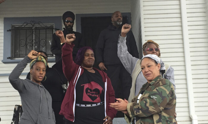 "In this Dec. 6, 2019 photo, Moms 4 Housing member Dominique Walker, 34, left, activist and 2018 Oakland mayoral candidate Cat Brooks, right, and other activists react as supporters chant ""power to the moms"" outside a home in West Oakland, Calif. (Marissa Kendal/Bay Area News Group via AP)"