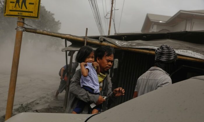 A family living near the erupting Taal Volcano evacuates in Lemery, Batangas City, Philippines, on Jan. 13, 2020. (Eloisa Lopez/Reuters)