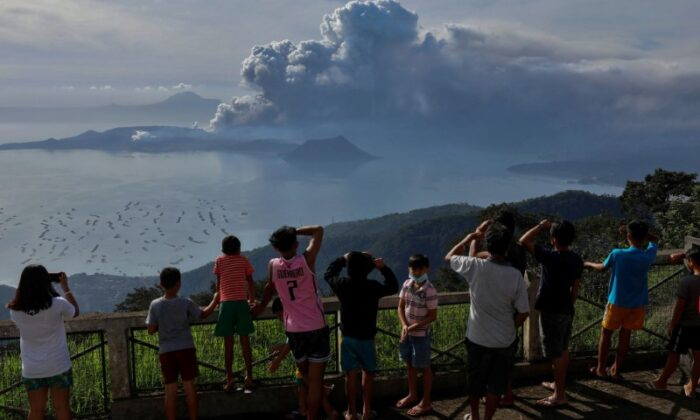 Residents look at the errupting Taal Volcano in Tagaytay City, Philippines, on Jan. 13, 2020. (Eloisa Lopez/Reuters)