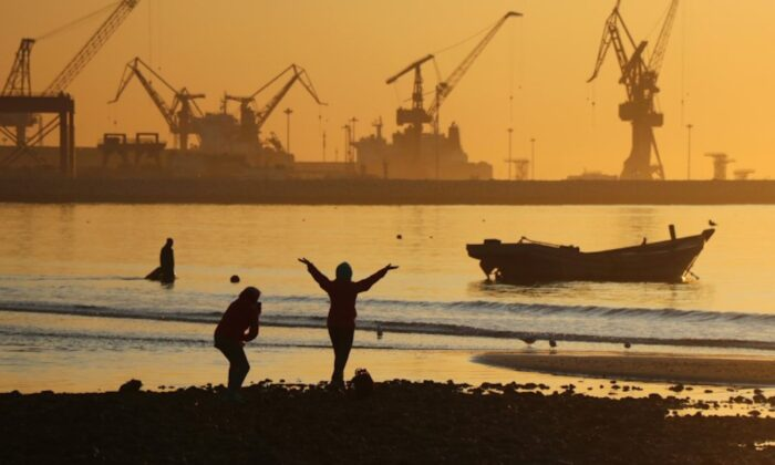 People enjoy the beach near a port during sunrise in Qinhuangdao, Hebei Province, China on Oct. 15, 2019. (Reuters)