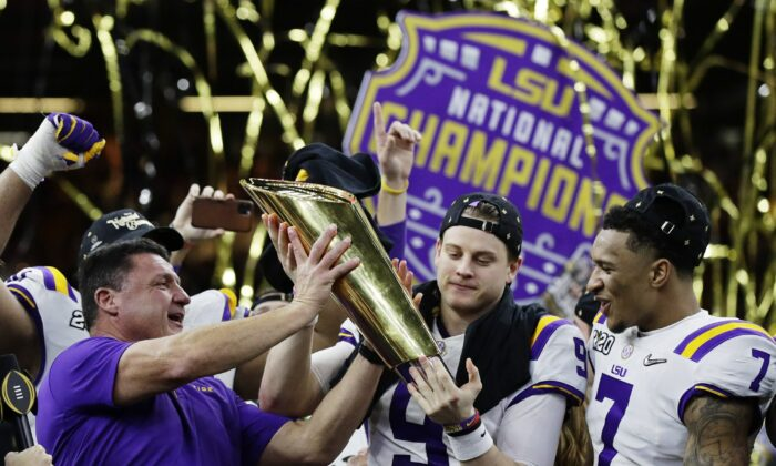LSU head coach Ed Orgeron, left, and quarterback Joe Burrow, center, hold the trophy beside safety Grant Delpit after a NCAA College Football Playoff national championship game against Clemson on Jan. 13, 2020, in New Orleans. LSU won 42-25. (Sue Ogrocki/AP Photo)