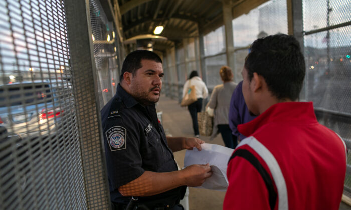 A U.S. Customs and Border Protection officer checks immigration documents as a Honduran asylum seeker arrives to the international bridge from Mexico to the United States next to the border town of Matamoros, Mexico, on Dec. 9, 2019.  (John Moore/Getty Images)