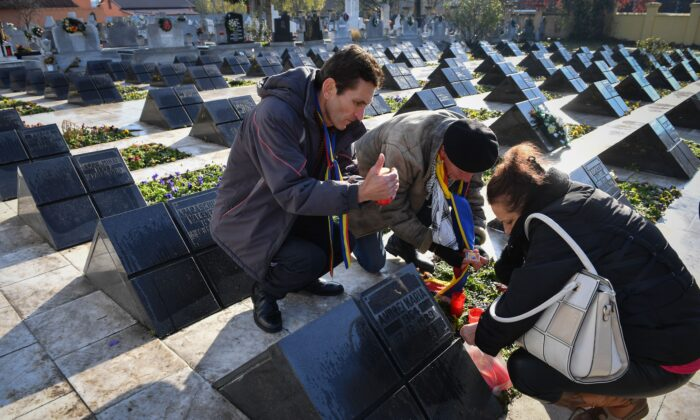 People light candles at the Heroes of the 1989 Revolution Cemetery to commemorate the 30th anniversary of the Romanian revolution's first victims in Timisoara, on Dec. 15, 2019. (DANIEL MIHAILESCU/AFP via Getty Images)