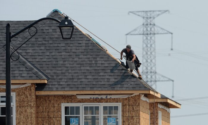 A construction worker shingles the roof of a new home in a housing development in Ottawa in a file photo. (The Canadian Press/Sean Kilpatrick)