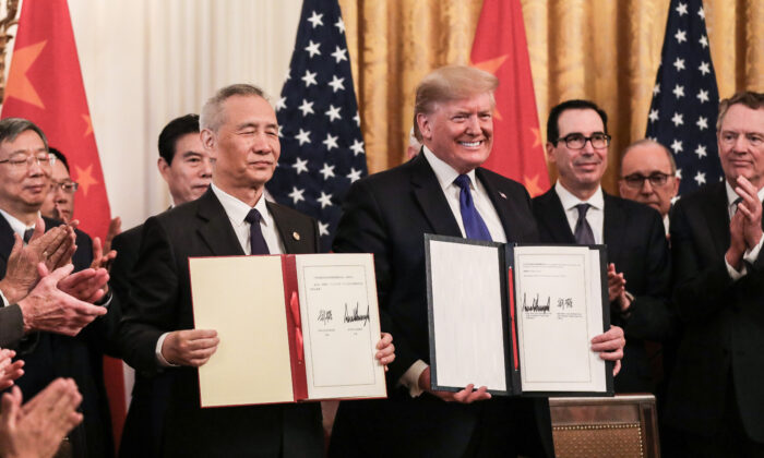Chinese Vice Premier Liu He (L) and President Donald Trump during the signing of phase one of a trade deal, surrounded by officials, in the East Room of the White House in Washington on Jan. 15, 2020. (Charlotte Cuthbertson/The Epoch Times)