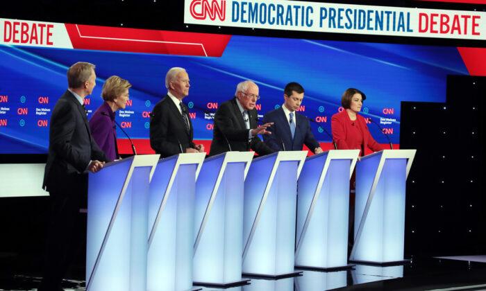 (L-R) Tom Steyer, Sen. Elizabeth Warren (D-Mass.), former Vice President Joe Biden, former South Bend, Indiana Mayor Pete Buttigieg and Sen. Amy Klobuchar (D-Minn.) listen as Sen. Bernie Sanders (I-Vt.) (3rd R) speaks during the Democratic presidential primary debate at Drake University in Des Moines, Iowa, on Jan. 14, 2020. (Scott Olson/Getty Images)