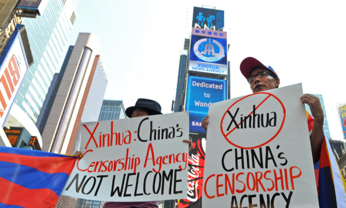 Students for a Free Tibet protest below a new electronic billboard leased by Xinhua (2nd from top), the news agency operated by the Chinese regime, as it makes its debut in New York's Times Square on Aug 1, 2011. (Stan Honda/AFP via Getty Images)