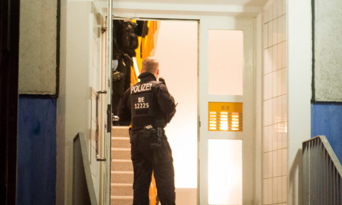 Policemen enter a residential building in Berlin's Marzahn-Hellersdorf district, where they carried out a raid, on Jan. 14, 2020. (Dennis Braetsch/DPA/AFP via Getty Images)