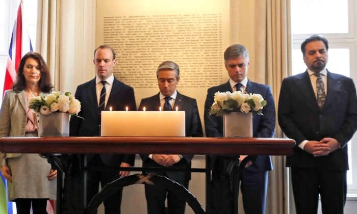 (L-R) Sweden's Minister of Foreign Affairs Ann Linde; United Kingdom's Secretary of State for Foreign Affairs Dominic Raab; Canada's Foreign Affairs Minister Francois-Philippe Champagne;  Ukraine Minister of Foreign Affairs Vadym Prystaiko; and Afghanistan's Foreign Minister Idrees Zaman, hold a minute of silence in front of a plaque with the names of the victims of flight PS752, at the High Commission of Canada in London on Jan. 16, 2020. (AP Photo/Frank Augstein)