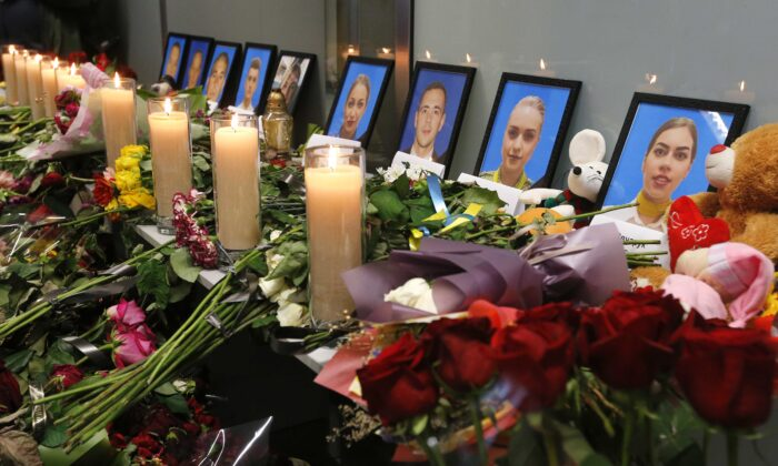 Flowers and candles are placed in front of portraits of the flight crew members of the Ukrainian 737-800 plane shot down by the Iranian military on the outskirts of Tehran, at a memorial inside Borispil international airport outside Kyiv, Ukraine, on Jan. 11, 2020.  (Efrem Lukatsky/AP Photo)