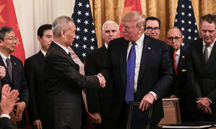Chinese Vice Premier Liu He (L) and U.S. President Donald Trump during the signing of phase one of a trade deal, surrounded by officials, in the East Room of the White House in Washington on Jan. 15, 2020. (Charlotte Cuthbertson/The Epoch Times)