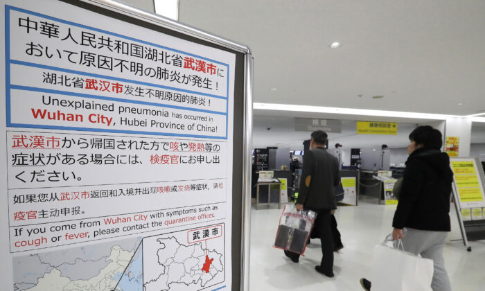 Passengers walk past a sign at Narita Airport in Chiba prefecture on January 16, 2020. Japan has confirmed a case of a mystery virus that first emerged in China and is from the same family as the deadly SARS pathogen, authorities said on January 16. (STR/JIJI PRESS/AFP via Getty Images)