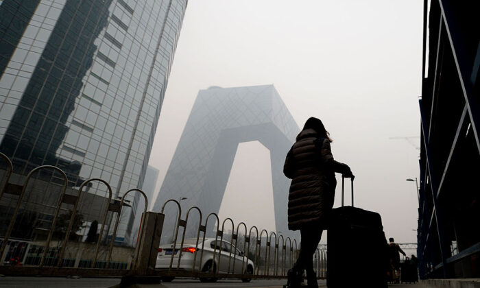 A woman walks past the new CCTV tower amid heavy smog in Beijing on Dec. 8, 2015. (STR/AFP via Getty Images)