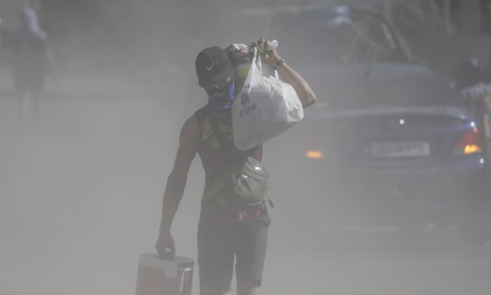 A man walks the his belongings through clouds of ash kicked up on a road as authorities enforced total evacuation of residents living near Taal volcano in Agoncillo town, Batangas province, southern Philippines on Jan. 16, 2020. (Aaron Favila/AP Photo)