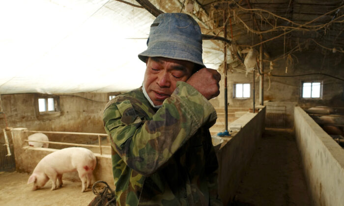 FILE PHOTO: Pig farmer Han Yi wipes his tears as he speaks to Reuters on his farm at a village in Changtu county, Liaoning province, China January 17, 2019. Picture taken January 17, 2019. REUTERS/Ryan Woo - RC1B97D839E0/File Photo