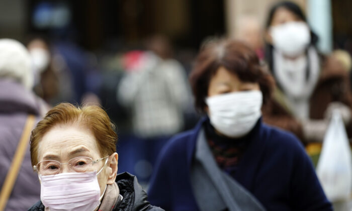 Pedestrians wear protective masks as they walk through a shopping district in Tokyo on Jan. 16, 2020. Japan's government said a man treated for pneumonia after returning from China has tested positive for the new coronavirus identified as a possible cause of an outbreak in the Chinese city of Wuhan. (Eugene Hoshiko/AP)
