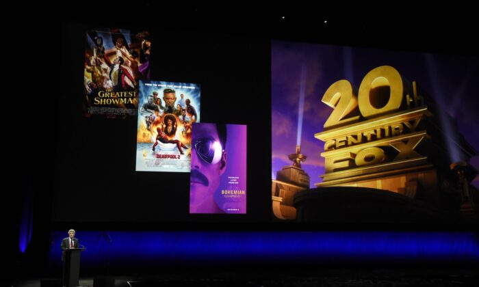 Alan Horn, chairman of The Walt Disney Studios, speaks underneath poster images for 20th Century Fox films during the Walt Disney Studios Motion Pictures presentation at CinemaCon 2019, the official convention of the National Association of Theatre Owners (NATO) at Caesars Palace in Las Vegas, Nev., on April 3, 2019. (Chris Pizzello/Invision/AP)