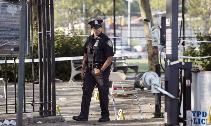 A police officer walks by yellow evidence markers at a playground after a shooting in the Brownsville neighborhood in Brooklyn, NYC, on July 28, 2019.  Mark Lennihan/AP Photo