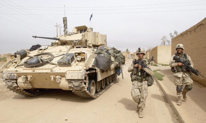 U.S. Army 3rd Division 3-7 infantry soldiers use a Bradley fighting vehicle for cover as they conduct a neighborhood patrol on the outside perimeter of the Baghdad International Airport April 8, 2003. (Scott Nelson/Getty Images)