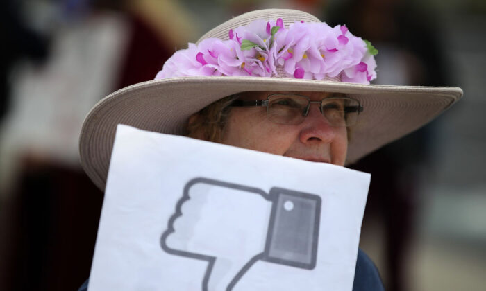 A protester holds a sign during a demonstration calling for better consumer protection and online privacy outside of Facebook headquarters in Menlo Park, Calif., on April 5, 2018. (Justin Sullivan/Getty Images)