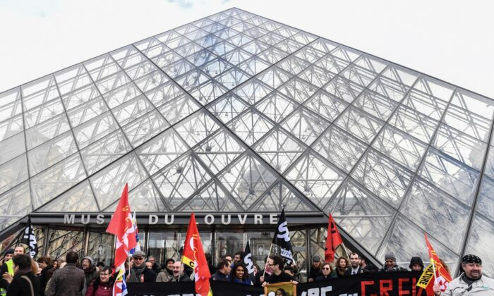 "Employees and members of French trade unions hold flags and a banner reading ""Musee du Louvre on strike"" in front of the Louvre pyramid at the entrance of Louvre museum, in Paris, France, on Jan. 17, 2019. (Alain Jocard/AFP via Getty Images)"