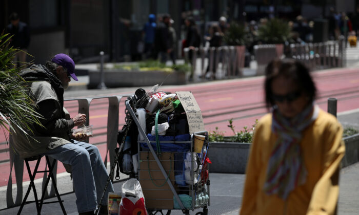 A pedestrian walks by a homeless man who is begging for money on May 17, 2019 in San Francisco, Calif. (Justin Sullivan/Getty Images)